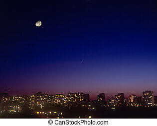 Night cityscape with moon.