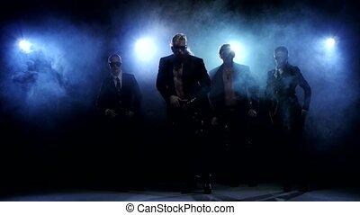 Night club dancers, man and woman posing in studio, smoke