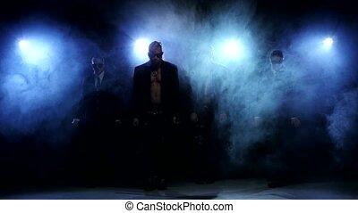 Night club dancers posing in studio, smoke