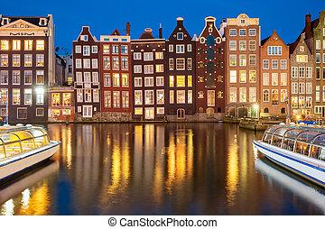 Night dancing houses at Amsterdam canal Damrak, Holland, Netherlands.