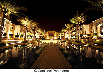 night Dubai street with palms and pool general view, United Arab Emirates