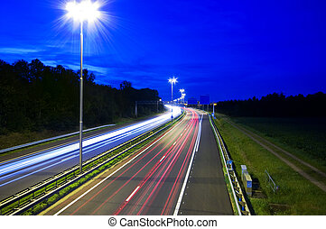 night highway - highway at night with rays of light passing...