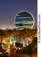Night illumination in the luxury hotel and circular building, Abu Dhabi, UAE