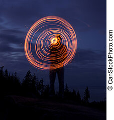 night image of a moving glow stick. - a person holding a ...