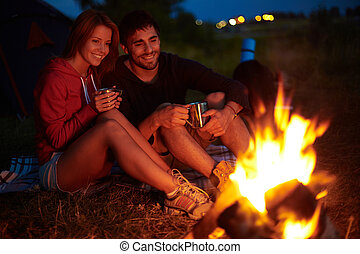 Night in camp - Young couple sitting on the ground and ...