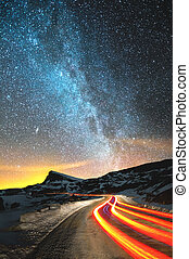 Night landscape. Night sky with a north hemisphere Milky Way and stars. The night road illuminated by the car winds with a serpentine and leaves in a distance to a foot of an acute rock. Light trails of red color. The concept of the path to knowledge and knowledge of the world.