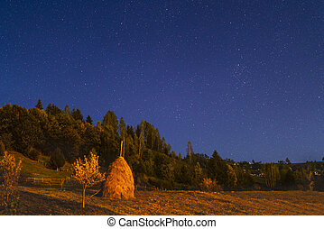 night landscape with haystack in the mountains