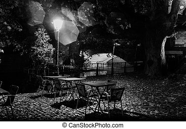 Night life , lonely empty restaurant tables under the city lights in the trees on the background of the illuminated bridge