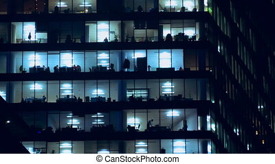Night life of office staff. - Large windows of the office...