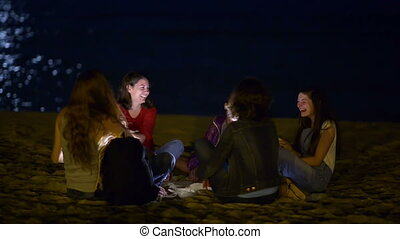 Group o young people spending the night on beach in the moonlight