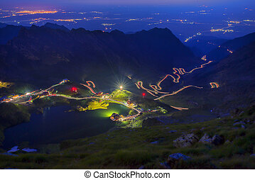 Night over mountain road and valley scene