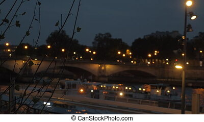 Night Paris view. The Seine with car bridge and sailing touristic water bus