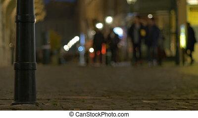 Night People on Cobblestone Street - Night pedestrians on...