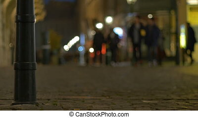 Night People on Cobblestone Street - Night pedestrians on...