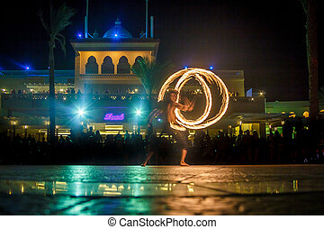 Night performance fire show in front of a crowd of people on the street in Egypt