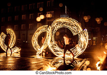 Night performance fire show in front of a crowd of people on the street in Russia