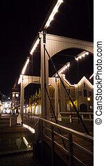 Night photo of illuminated wooden bridge over canal