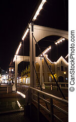 Night photo of illuminated wooden bridge over canal