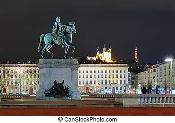 Equestrian statue of Louis XIV on the Place Bellecour, Basilica of Notre-Dame de Fourviere on the background at night in Lyon, France