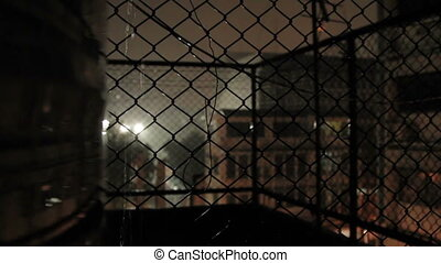 Night rain in Bangkok. View on wet street from balcony through rabitz net. Thailand.