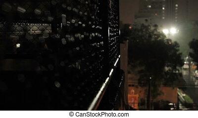 Night rain in Bangkok. View on wet street from balcony through rabitz net.