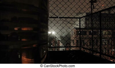 Night rain in Bangkok. View on wet street from balcony through rabitz net. Thailand.