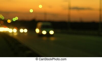Night road with blurred cars headlights and orange sunset...