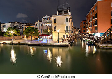 Night scene of illuminated old buildings, floating boats and reflections in canal water in Venice, Italy.