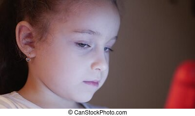 Night Shot of a Cute Caucasian Little Girl Close Up of a Child's Face Viewing a Tablet PC With a Reflection of Pight and Pictures in His Eyes