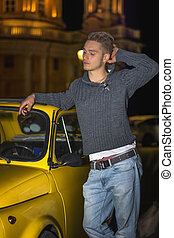 Night shot of young man standing next to small car