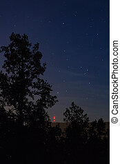 NIght sky with stars and tree silhouette and hill Klet
