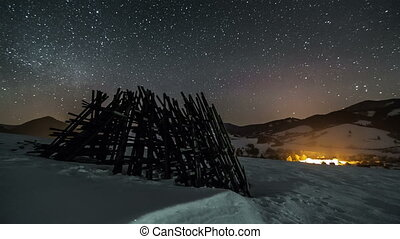 Night sky with stars moving over winter rural country with wooden frame, astronomy time lapse, dolly shot over snow