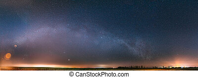 Night Starry Sky With Glowing Stars Above Countryside Landscape. Milky Way Galaxy And Rural Field Meadow In Early Spring. Panorama, Panoramic View