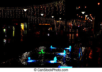 Night street in the city is decorated with a luminous garland and a fountain with lighting. Decoration of the city in Israel to Hanukkah and the New Year