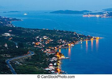 Night summer coastline and village on seashore
