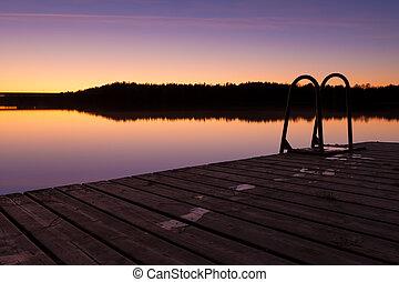 Night swim dock and calm lake at twilight
