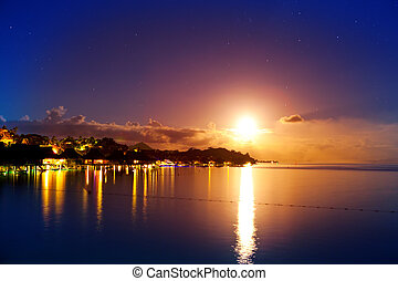 Night. The moon over the sea and reflection in water. Bora-Bora