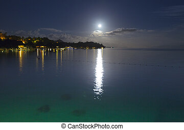 Night. The moon over the sea and reflection in water.