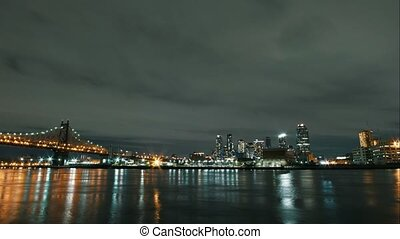 Night time-lapse of Manhattan skyscrapers from water, wide...