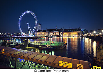 Night time view of the South Bank of the Thames, London including the London Eye, County Hall and Westminster Millennium Pier