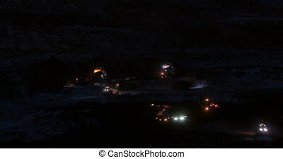 Night timelapse, excavators dig coal in the quarry. The dump trucks come and take away the coal.