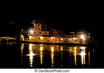 Closeup of tug boat on river moving barges at night time