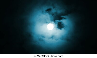 Night view at the moon through blue moving clouds