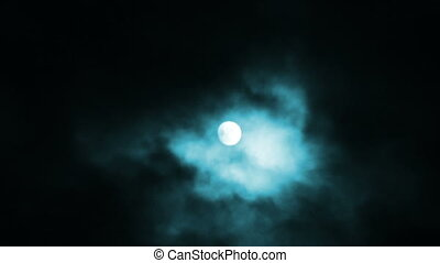 Night view at the moon through moving clouds.