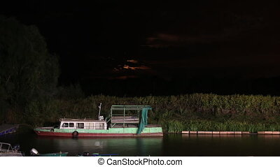 Night view of a harbor with the old boat and a moon rising in the background. Time lapse 1080p