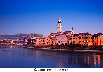 Night view of Adige River and riverside apartments. Verona Cathedral and Castel San Pietro are also visible.