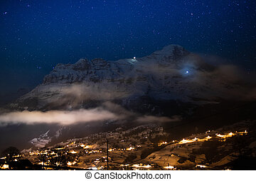 View of Eiger north face, Alps, Switzerland on clear starry night. Eiger Nordwand mountain in Swiss Bernese Alps. Mountains and snowy village in winter time with Christmas lights. Blue sky with stars.
