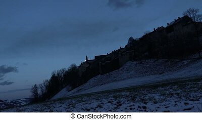 Night view of Gruyere Castle with moon. Time lapse with wide angle lens in Switzerland. Idyllic and tranquil scene.