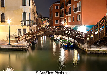 Night view of illuminated old architecture, floating boats and light reflections in canals water in Venice, Italy.
