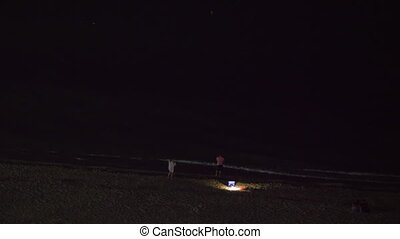 Night view of people relaxing on beach and looking dark sea